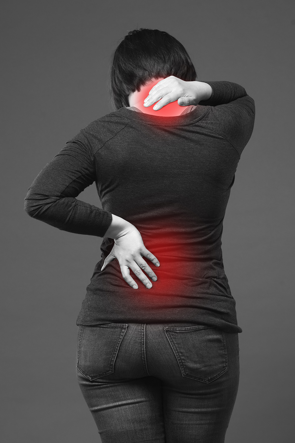 Back pain, woman with backache on gray background, black and white photo with red spots